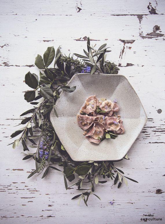 Ravioli alla barbabietola ripieni con formaggi, rucola e noci. Una ricetta rosea e vegetariana.